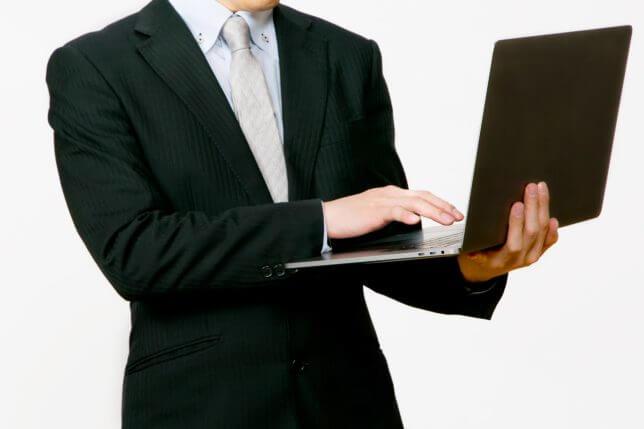 ノートPCを持つ男性