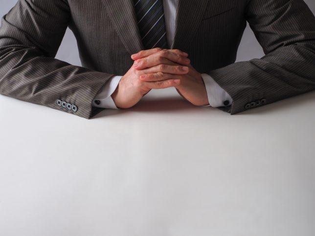 机の上で腕を組むイメージ