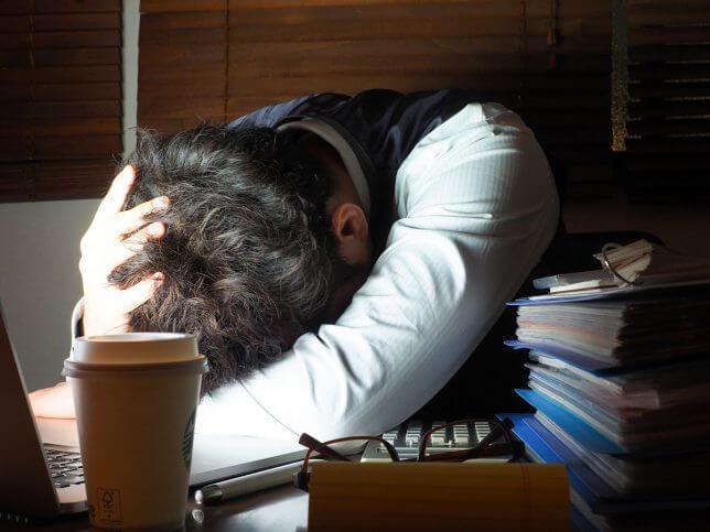 机の上で寝る男性