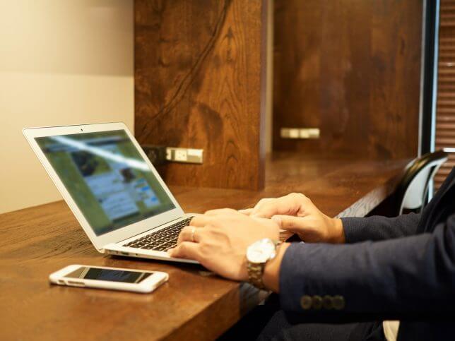 机の上でノートPCを操作