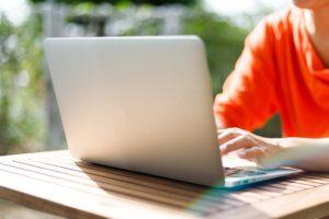 赤い服の女性がパソコンを操作する